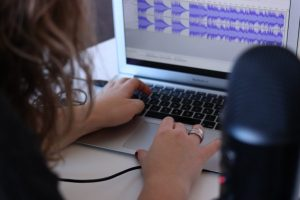 picture of podcaster editing their podcast using editing software